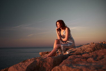 Chris Reeve DAYDREAMING WOMAN ON ROCKY BEACH AT SUNSET Women