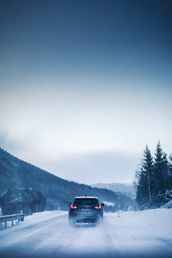 Des Panteva CAR ON SNOWY ROAD WITH MOUNTAINS Cars