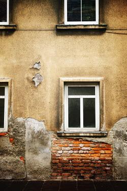 Irene Lamprakou WEATHERED HOUSE WITH BRICKS AND PEELING PLASTER Houses