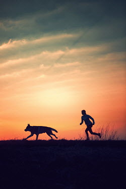 Magdalena Russocka silhouettes of woman and dog running at sunset Women
