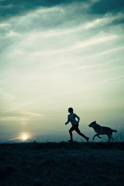Magdalena Russocka silhouette of woman and wolfdog running at sunset Women