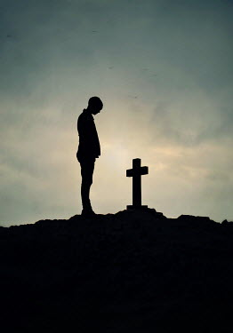 Lyn Randle SILHOUETTED MAN BY GRAVESTONE AT DUSK Men