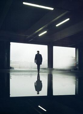 Mark Owen MAN WALKING IN CARPARK REFLECTED IN PUDDLE Men