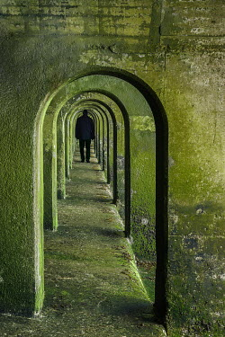 Tony Watson SILHOUETTED MAN WALKING IN ARCHED TUNNEL Men