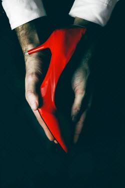 Ildiko Neer Red high heel in man's hands