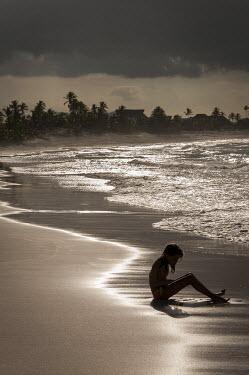 Tim Gartside YOUNG GIRL SITTING ON SANDY BEACH Children