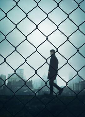 Mark Owen MAN WALKING BEHIND FENCE NEAR CITY Men