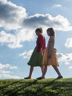 Elisabeth Ansley Two girls holding hands on grass Children