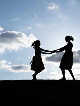 Elisabeth Ansley Two girls holding hands in field Children