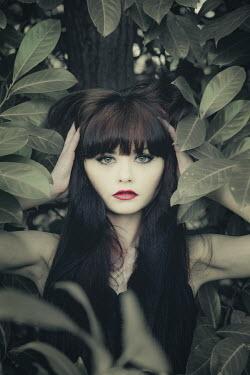 Nic Skerten BRUNETTE GIRL BY TREE BEHIND LEAVES Women