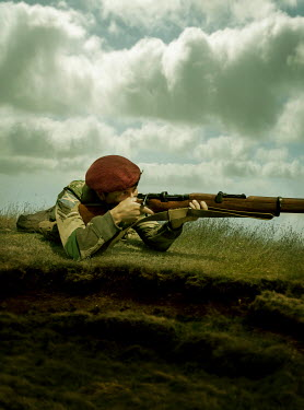 Stephen Mulcahey SOLDIER AIMING RIFLE LYING ON GRASS Men