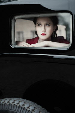 Magdalena Russocka retro woman looking out rear window of classic car