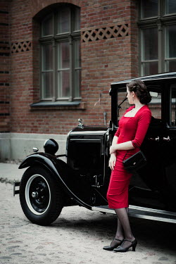 Magdalena Russocka retro woman leaning against classic car
