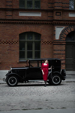 Magdalena Russocka retro woman in red dress standing by classic car