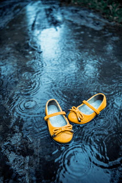 Magdalena Russocka Yellow childrens shoes in water Miscellaneous Objects