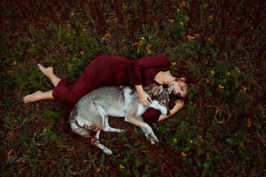 Nathalie Seiferth Woman and wolf lying on grass Women