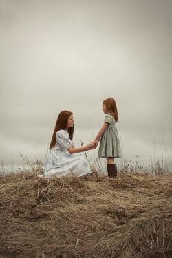 Robin Macmillan Two girls holding hands in field Children