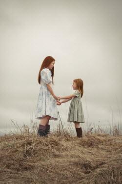 Robin Macmillan Two girls holding hands in grass Children