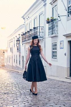 Chris Reeve Retro woman walking in cobbled street Women