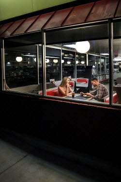 Stephen Carroll COUPLE SITTING IN RESTAURANT AT NIGHTTIME Couples