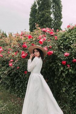 Jovana Rikalo Woman in dress by flower bush Women