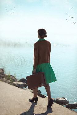 Ildiko Neer Vintage woman walking by lake with suitcase