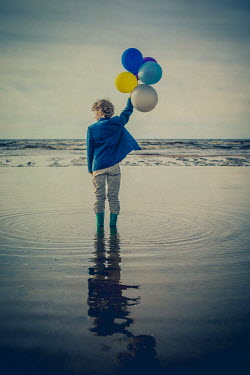 Katya Evdokimova BOY STANDING IN SEA HOLDING BALLOONS Children