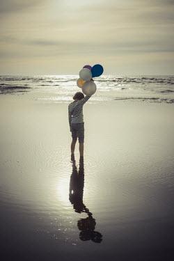 Katya Evdokimova BOY IN SEA AT DUSK HOLDING BALLOONS Children