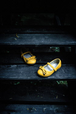Magdalena Russocka child's yellow shoes on wooden steps