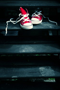 Magdalena Russocka pair of red sneakers on wooden steps