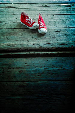 Magdalena Russocka pair of red sneakers left on old wooden floor