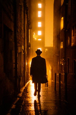Laurence Winram SILHOUETTED MAN WALKING IN CITY AT NIGHT Men