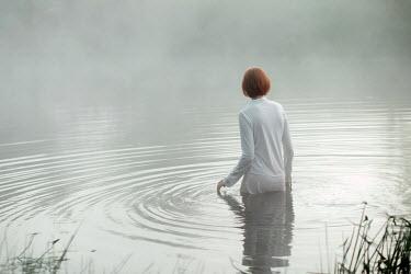 Alexander Kuzovkov Clothed woman walking in water Women
