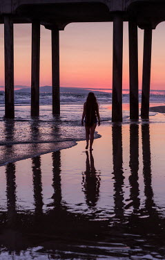 Maggie McCall SILHOUETTED WOMAN UNDER PIER AT SUNSET Women