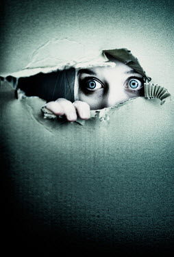 Magdalena Russocka scared woman looking through hole in cardboard