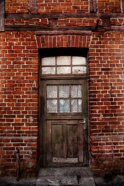 Kerstin Marinov WOODEN DOOR IN HISTORICAL RED BRICK HOUSE Houses