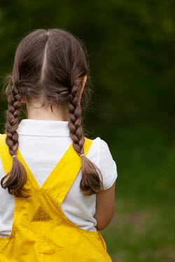 Kerstin Marinov LITTLE GIRL WITH PLAITS IN DUNGAREES OUTDOORS Children