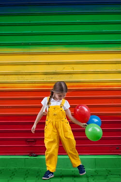 Kerstin Marinov girl with colourful balloons and wall Children