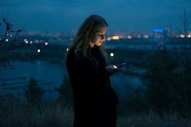 Dmitriy Bilous WOMAN LOOKING AT PHONE AT NIGHT Women