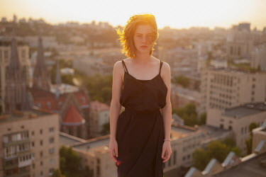 Dmitriy Bilous WOMAN STANDING ON ROOFTOP AT SUNRISE Women