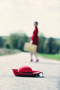 Magdalena Russocka red hat dropped on country road and blurred retro woman