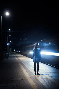 Magdalena Russocka woman standing by moving train at night Women