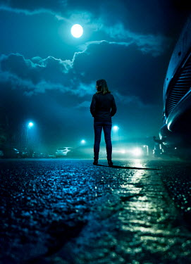 Stephen Mulcahey Woman's silhouette in nighttime car park Women