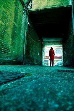 Stephen Mulcahey Woman standing in covered alleyway Women