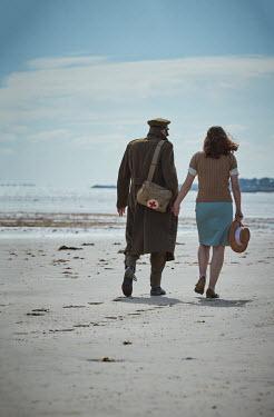 CollaborationJS A ww2 couple walking along a beach Couples