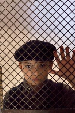 Kerstin Marinov RETRO BOY LOOKING THROUGH WIRE FENCE Children