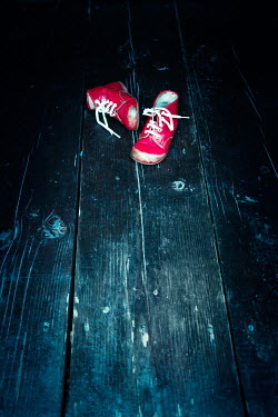 Magdalena Russocka child's red shoes left on wooden floor