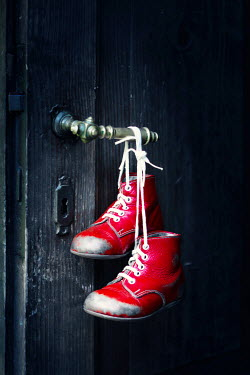 Magdalena Russocka childs red shoes hanging on door handle