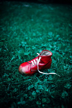 Magdalena Russocka child's red shoe lying on grass