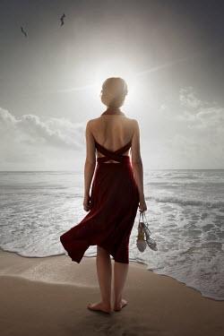 ILINA SIMEONOVA GIRL CARRYING SANDALS ON BEACH AT DUSK Women